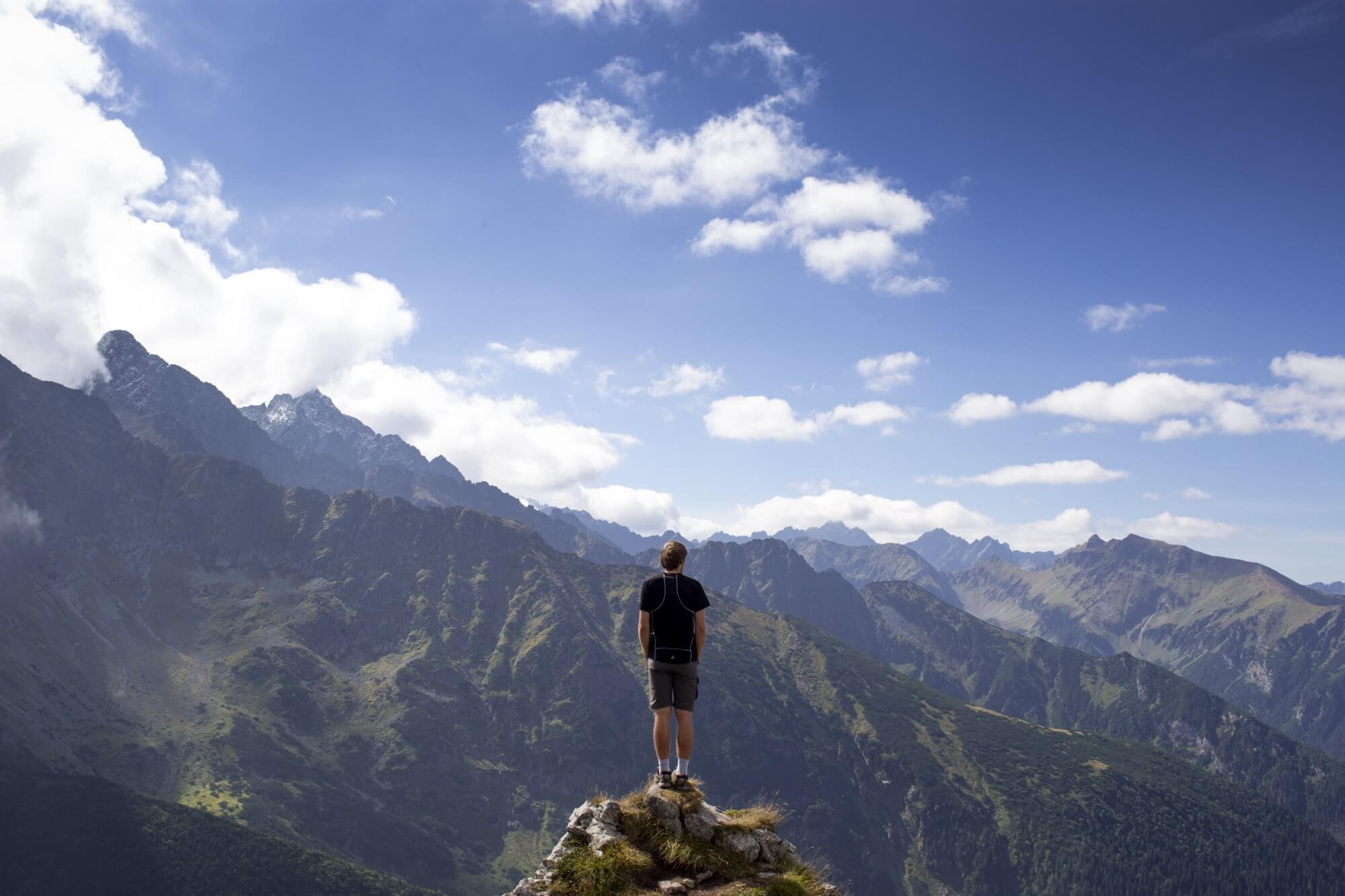 Man standing on point of a mountain overlooking nature with a cloudy sky in the background