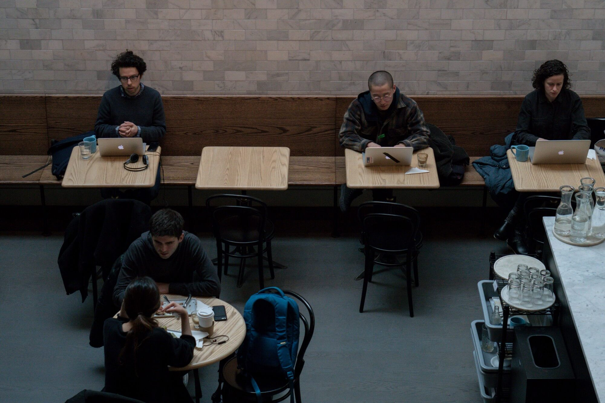 Group of individuals sitting at different tables in a coffee shop working
